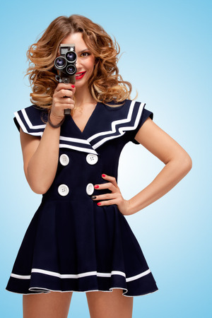 Retro photo of a glamorous pin-up sailor girl with an old vintage cinema 8 mm camera, looking like a sexy producer, shooting a movie on blue background.