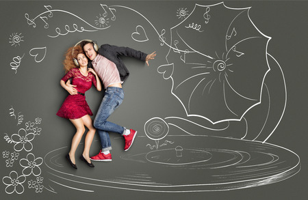 Happy valentines love story concept of a romantic couple sharing headphones, listening to the music and dancing on a gramophone, against chalk drawings background.