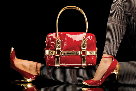 Photo pour A close-up of a chic red handbag along with sexy female legs wearing elegant red shoes. - image libre de droit
