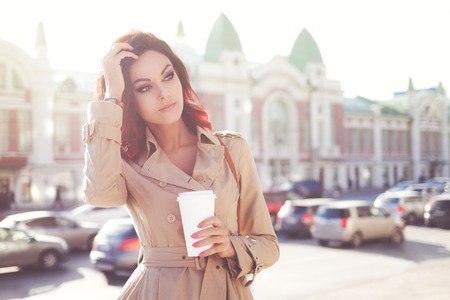 Beautiful young woman in a modern trench coat, holding a disposable takeaway cup and standing against urban city background.