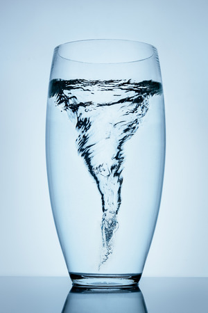 Magnificent tornado made of water in a transparent glass standing on the reflective surface.