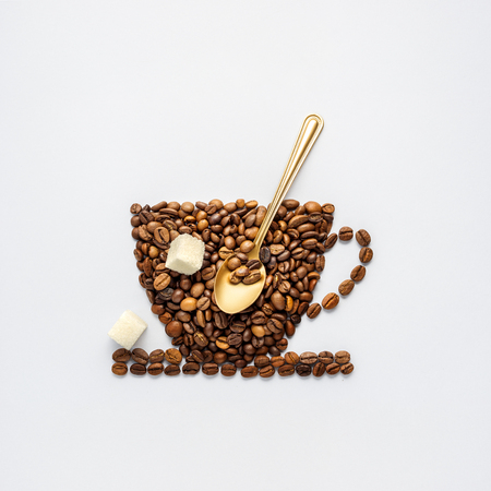 Foto de Creative concept photo of coffee cup made of beans with spoon and sugar on grey background. - Imagen libre de derechos