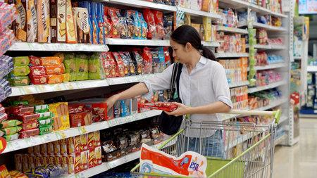 Asian girl, woman shopping snacks in supermarket