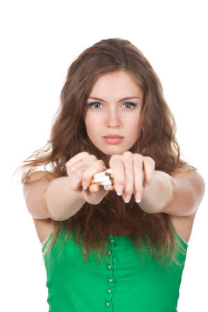 Pretty young woman breaking cigarette isolated over white