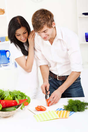 young lovely couple in their kitchen coocking happy smile