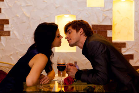 Young happy couple romantic kissing date with glass of red wine at restaurant, celebrating valentine day