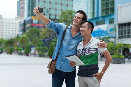 Two men tourists taking selfie photo smile, asian mix race