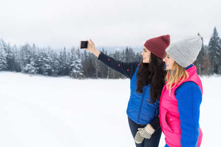 Two Girl Taking Selfie Photo On Smart Phone Snowy Mountain Young Woman Winter Snow Holiday Vacation