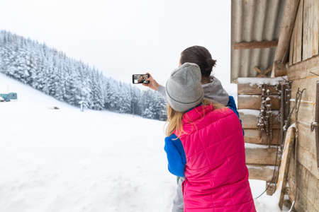 Couple Taking Selfie Photo On Smart Phone Snowy Village Wooden Country House Man Woman Winter Snow Resort Cottage