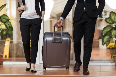 Foto de Business Couple In Hotel Lobby, Businesspeople Group Man And Woman Guests Arrive Entrance With Suitcase - Imagen libre de derechos