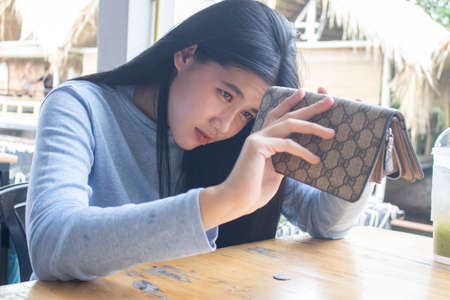 Photo for poor Asian woman open empty purse looking for money having problem with payment or debt, - Royalty Free Image