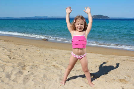 little girl with hands up standing on the beach