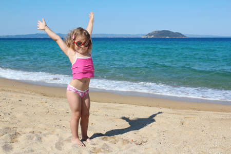 happy young girl with hands up on the beach