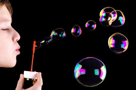 Boy blowing bubbles on the black background