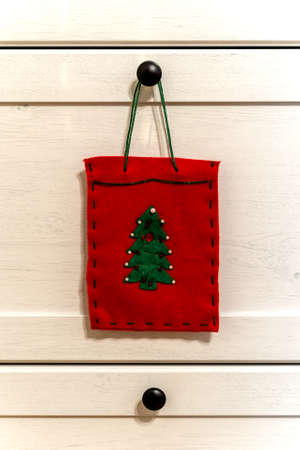 Photo pour A red felt decorative bag with a green christmas tree, even with its own decoration, hangs on a white cupboard with black knobs during christmas time. - image libre de droit