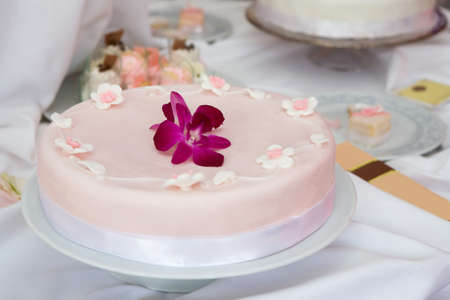 Wedding cake with pink icing decorated with an orchid flower