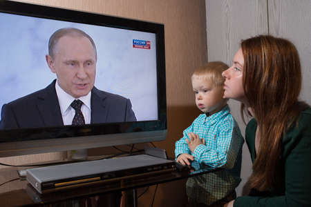 St. Petersburg, Russia - December 3, 2015: Mother and young son watching on television the message of President Vladimir Putin to the Federal Assembly