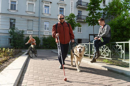 Photo pour St. Petersburg, Russia - May 29, 2012: A blind man of 50 years during training walking around the city with the help of a guide dog breed Labrador on the main street. - image libre de droit
