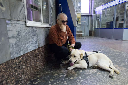 St. Petersburg, Russia - July 17 2015: School to teach the blind to use the subway with dogs allowed. Blind man with a dog at the box office Metro.