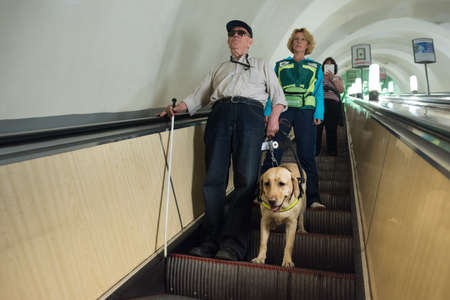 St. Petersburg, Russia - July 17 2015: School to teach the blind to use the subway with dogs allowed. Blind man with guide dog on the escalator with instructor