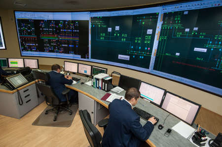 Saint-Petersburg, Russia - September 22, 2016: Top view of the office managing the power company. Energy engineers work at computers monitor the city grid.