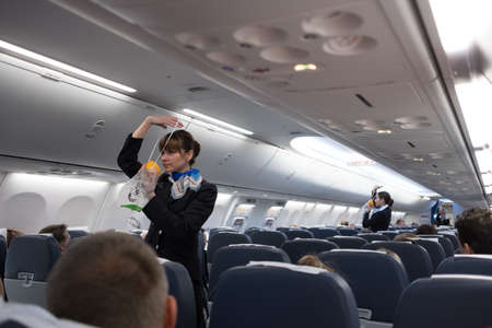 Photo pour St. Petersburg, Russian Federation - October 16, 2017:  Stewardesses  in the cabin of the 737-800 passenger airplane instruct passengers on safety measures and  in the event of an emergency - image libre de droit