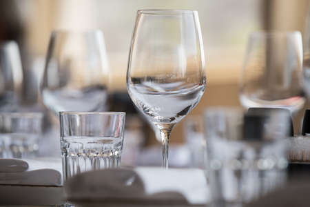 In the restaurant there are wine glasses in the , cutlery, napkins and other items for food, arranged by the catering service on a large table covered with white scarette