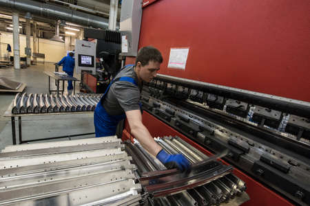 St. Petersburg, Russia - June 29, 2016: A shop for processing steel, aluminum and zinc sheets used to build the bodies of subway cars at a transport engineering plant. The worker controls the work of the machine.