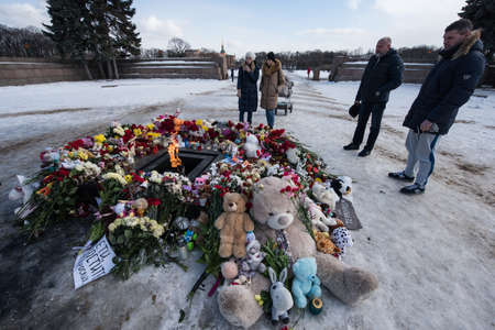 St. Petersburg, Russia -28 March 2018: Flowers and children's toys are laid to eternal fire on the Champ de Mars on the day of mourning and tragedy in Kemerovo, where people died in the Winter Cherry mall