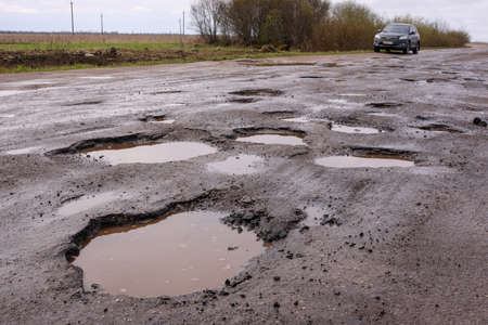 Photo for Novgorod Region, Russia-May 1, 2018: The road of local importance in emergency condition with a lot of potholes flooded with rain. Cars go with the risk of breakdowns - Royalty Free Image