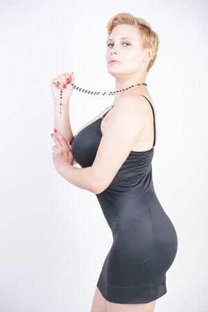 Photo pour Portrait of attractive chubby young woman in tight black dress - image libre de droit