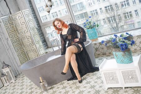Foto de pin up woman on vintage bathtub in bathroom with big window - Imagen libre de derechos
