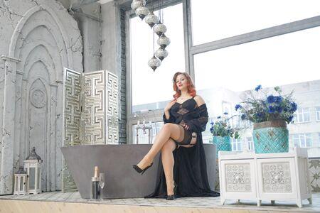 Foto de pin up woman on vintage bathtub in bathroom with big window - Imagen libre de derechos