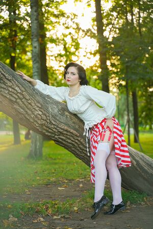 Photo for Close-up of a happy young pin up girl posing with tree at the park - Royalty Free Image