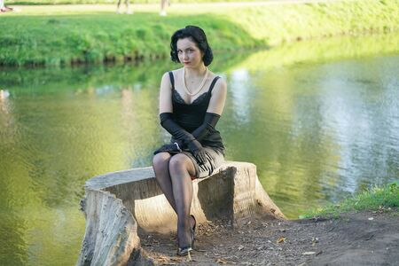 Foto de Outdoor portrait of pinup girl sitting on stump in the city park near the water - Imagen libre de derechos