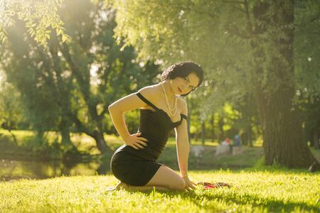 Photo pour Beautiful young woman with pin-up make-up and hairstyle posing in the summer city park - image libre de droit