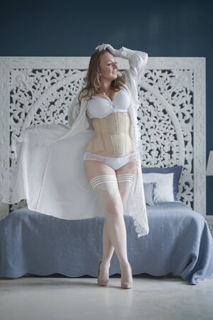 Foto de sexual plus size bride girl in white lingerie in the bedroom alone. chubby woman in lace underwear with corset and stockings alone - Imagen libre de derechos