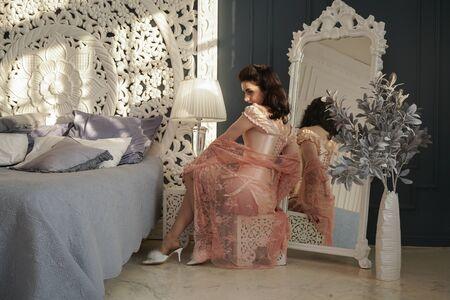 Foto de pretty slim girl in very tight pink satin corset near the mirror in her rich apartment - Imagen libre de derechos