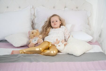 Photo pour portrait of a sad girl with unhappy face sitting on a bed in the bedroom - image libre de droit