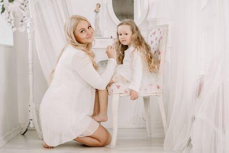 Foto de Beautiful woman and child girl doing make up each other on white room background - Imagen libre de derechos