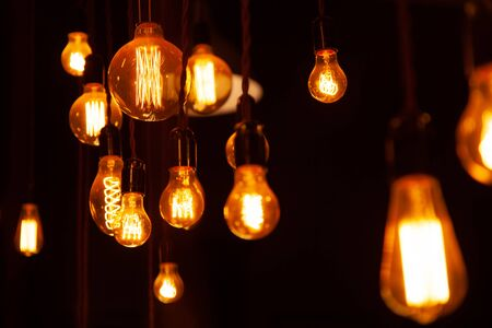 Photo for classic different retro light bulbs hanging on brick wall background at night - Royalty Free Image