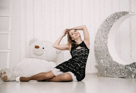 Photo pour pretty adult girl with big white teddy bear alone - image libre de droit