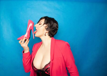 Foto de Plus size short hair brunette sexy Women loves pink patent leather high heels shoes and holds it with exciting pleasure on blue background - Imagen libre de derechos