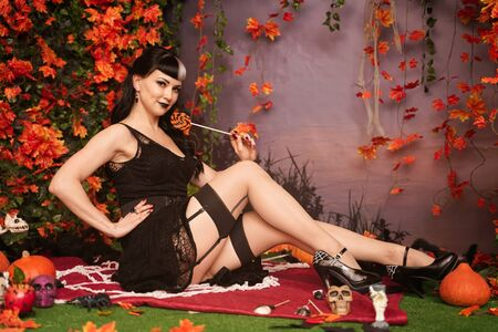 Foto de Slim fashion halloween girl with black hair in lace gothic pin up dress posing in the autumn background with fall leaves - Imagen libre de derechos