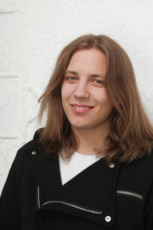 Portrait of young handsome man with beautiful long hair