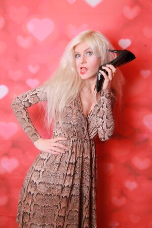 Photo for Young amazed woman using a shoe like a telephone holding it near her face and talking, red background. Pin-up style. - Royalty Free Image