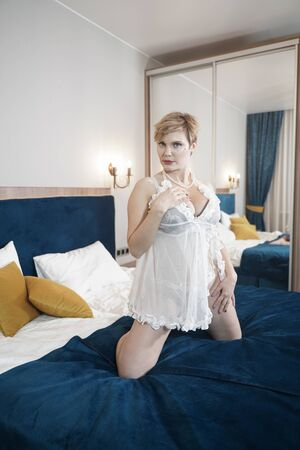 Foto de sexy blonde plus size short hair woman in lingerie transparent dress on bedroom background - Imagen libre de derechos