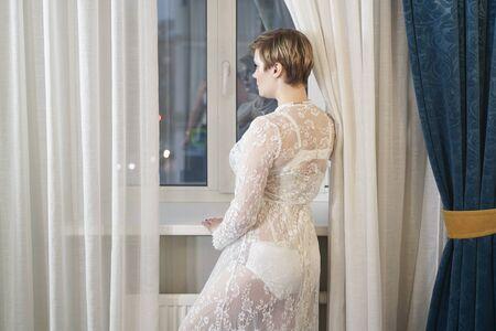 Foto de sexy blonde plus size short hair woman in lingerie transparent dress on bedroom background - Imagen libre de derechos
