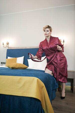 Foto de stylish pin up short hair blonde woman with plus size curvy body posing in fashion red bathrobe in the bedroom alone - Imagen libre de derechos