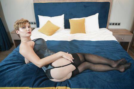 Foto de stylish pin up short hair blonde woman with plus size curvy body posing in fashion underwear in the bedroom alone - Imagen libre de derechos